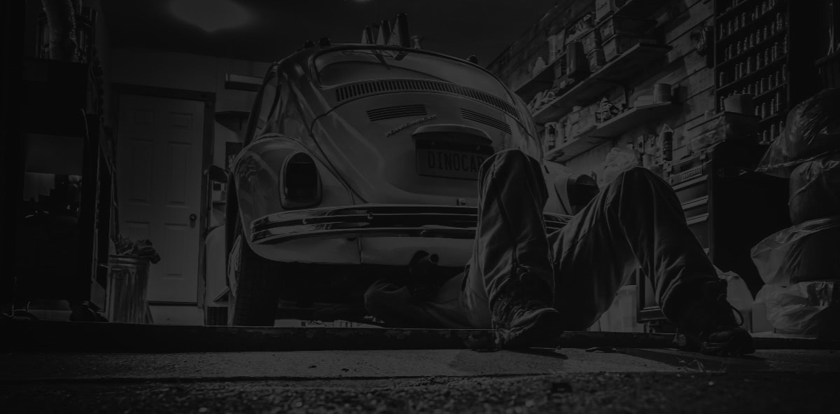 Background image of a mechanic fixing a car