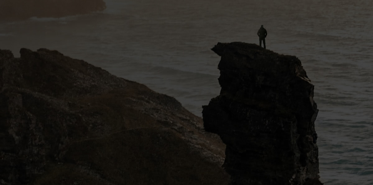 Background image of a person standing on a cliff top.